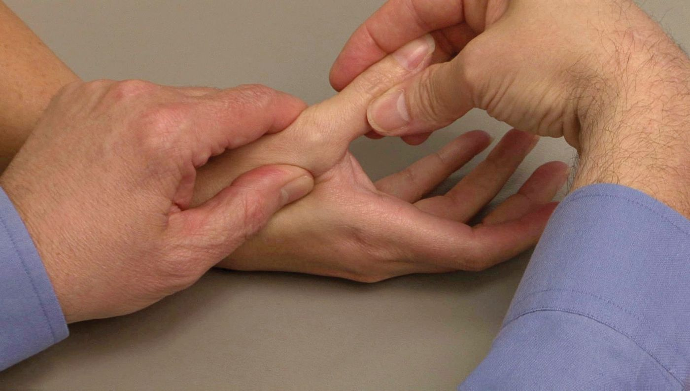 Doctor applying tension on thumb joint